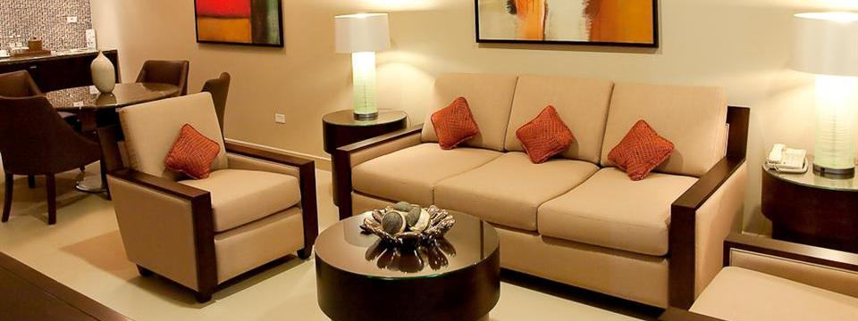 Suite living area with sleeper sofa, dining table and artwork