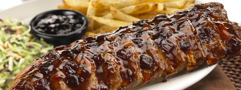 Plate of barbecue glazed ribs, coleslaw and fries
