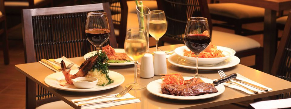 Table set with an assortment of entrées and glasses of wine