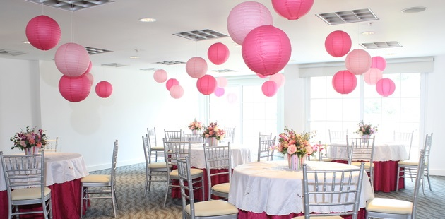 Meeting room with round tables and pink paper lanterns dangling from ceiling