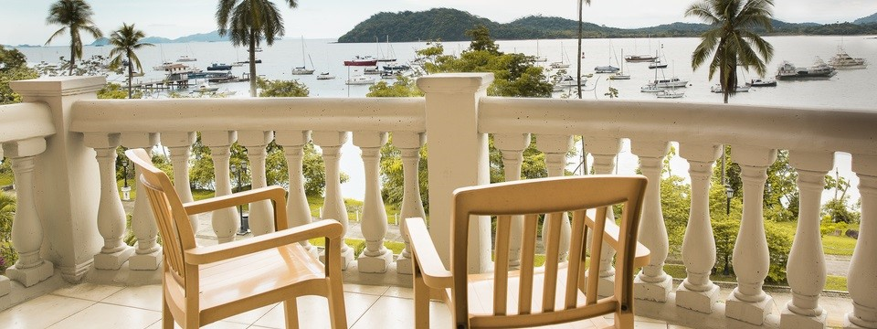 Hotel balcony with chairs offering views of ocean