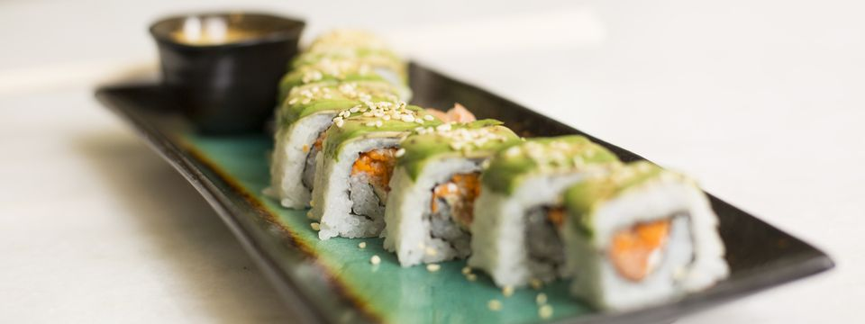 Sushi roll topped with avocado and sesame seeds
