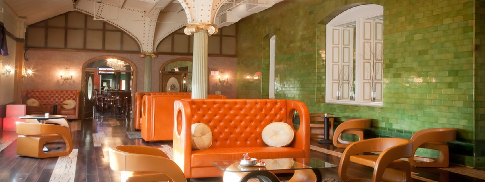 Green brick walls and orange banquette seating in restaurant