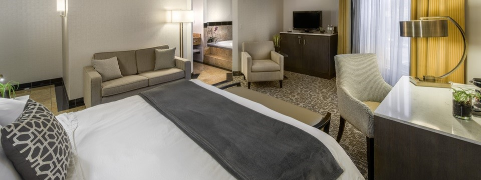 Hotel suite with a whirlpool tub, a king bed, a sleeper sofa and two chairs