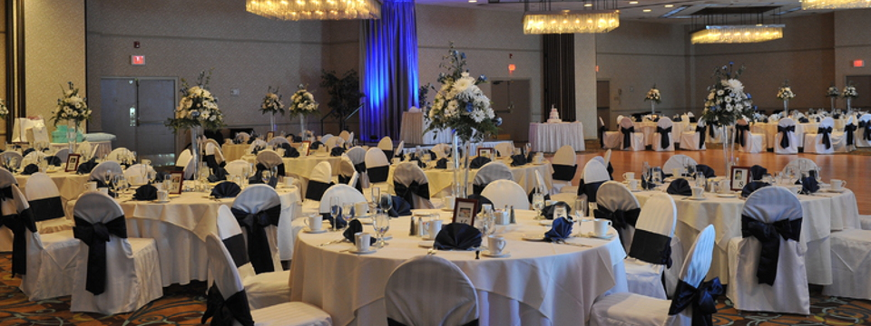 Hotel ballroom set up with round tables, blue accents and large floral displays