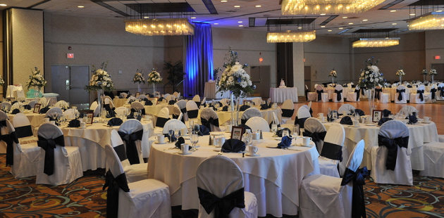 Hotel ballroom set up for a wedding reception with elegant floral displays
