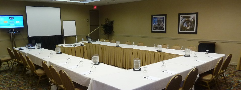 Hotel's Pine Meeting Room with a U-shape table setup and projector screen