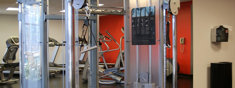 Hotel fitness center with a weight machine and a red accent wall