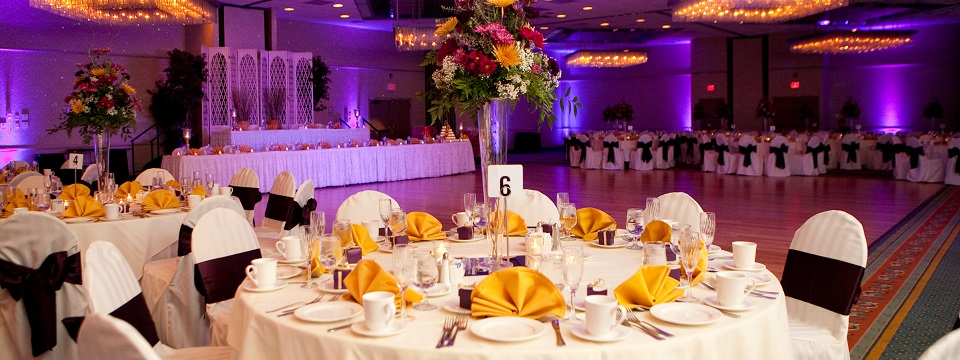 Hotel ballroom with dance floor, round tables and head table
