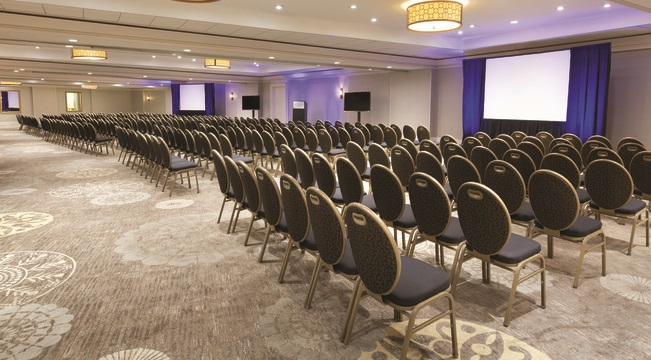 Hotel meeting space with rows of chairs facing a presentation screen