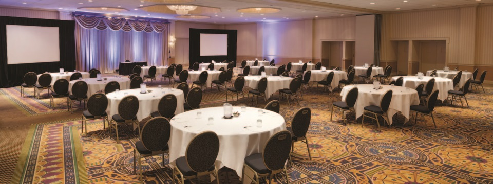 Grand Ballroom set up with round tables and projector screens