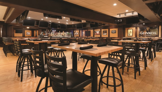 Valley Tavern pub with black chairs and rows of flat-screen TVs