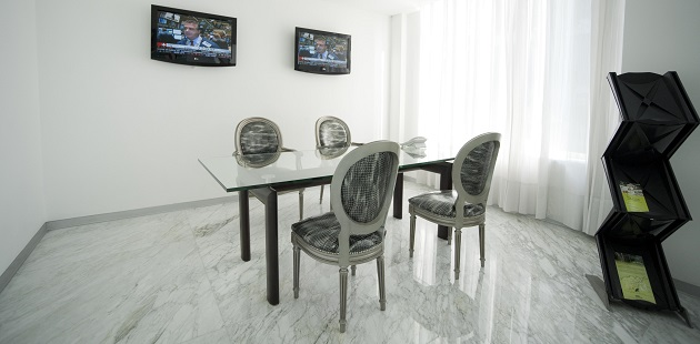 Intimate meeting room with white walls and two TVs