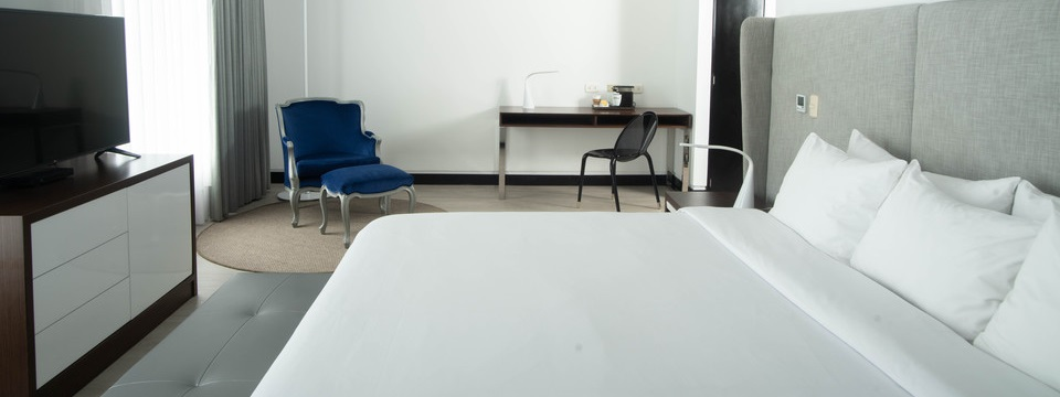 Studio Suite featuring a king bed, a work desk and a blue armchair with a blue ottoman