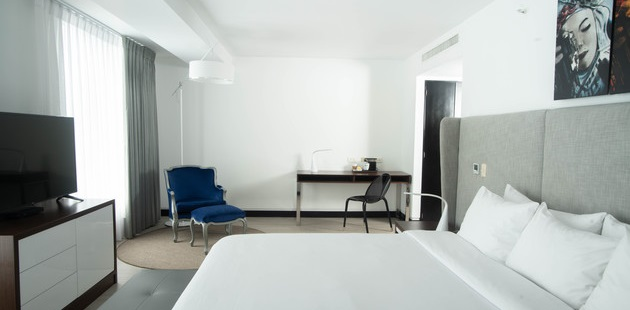 Studio Suite featuring a king bed, a flat-screen TV, a work desk and a blue armchair with an ottoman