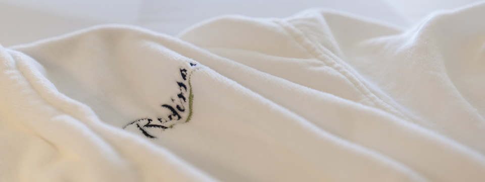 Plush, white robe featuring the Radisson logo