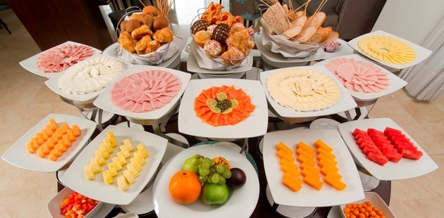 Breakfast spread featuring fruits, meats and breads
