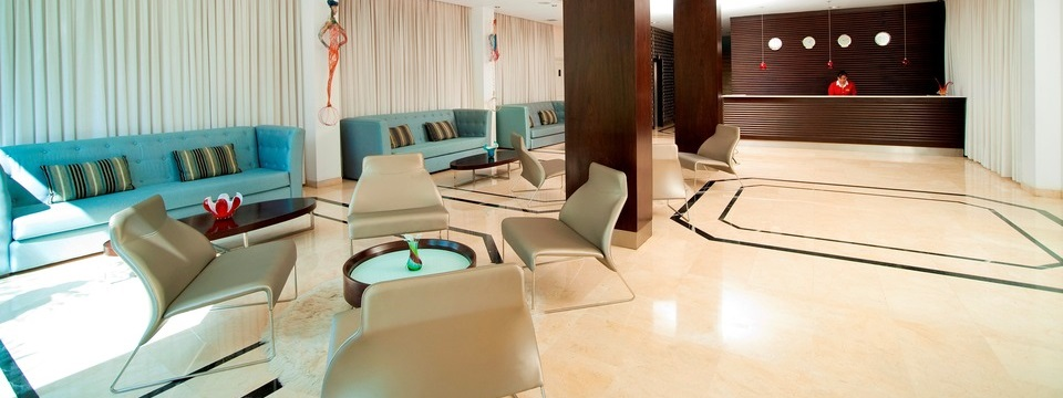 Contemporary lobby featuring comfy teal couches and a reception desk