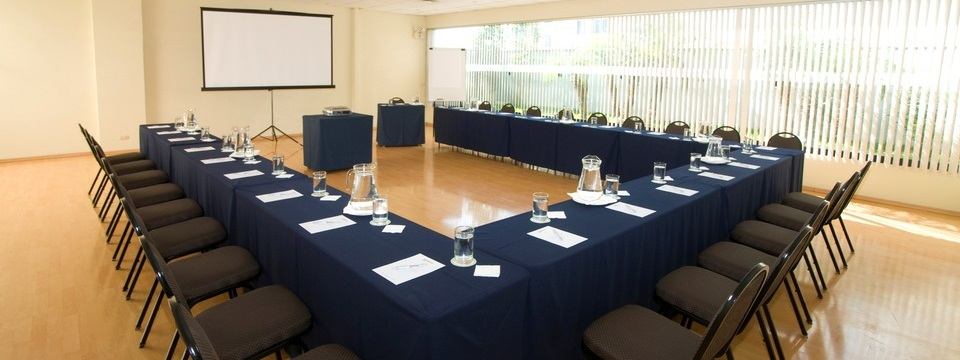Modern meeting space with projection screen and blue tablecloths