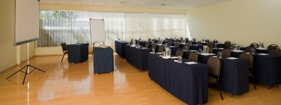 Meeting facilities with natural lighting and rows of tables facing a white screen
