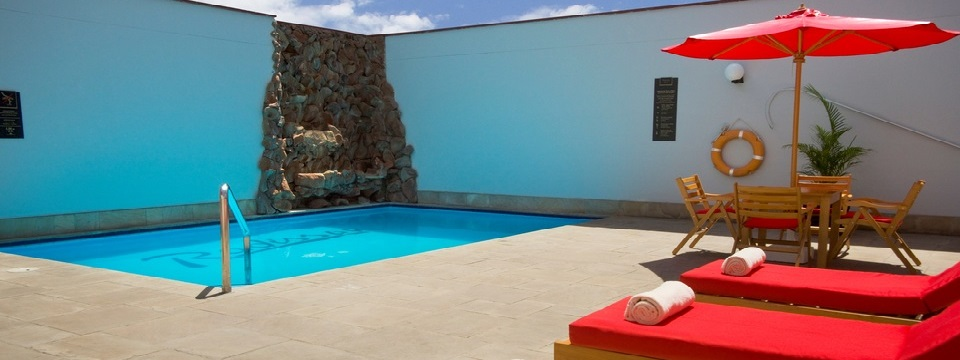 Outdoor pool with stone waterfall feature and red lounge chairs