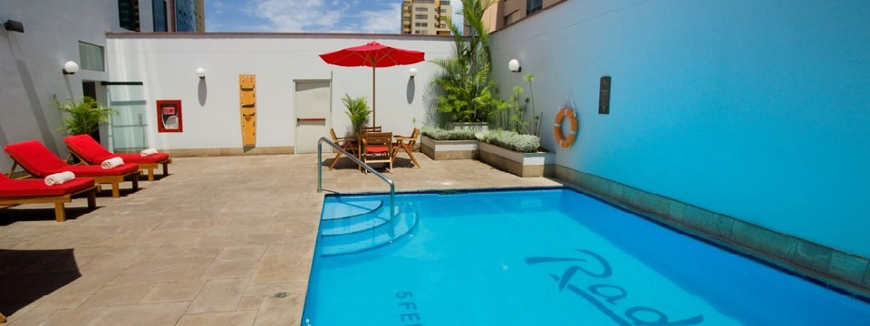 Outdoor pool and patio area with red lounge chairs