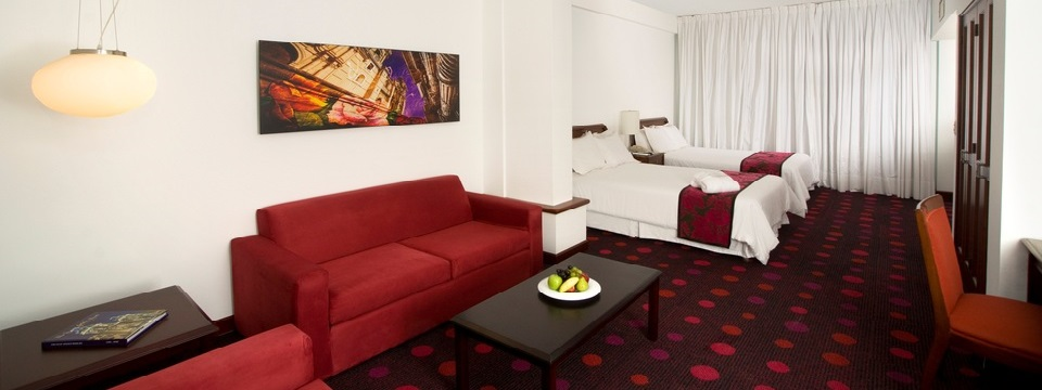 Hotel suite with two double beds and a red couch