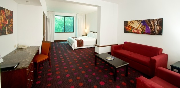 Hotel suite with red carpeting and red couch