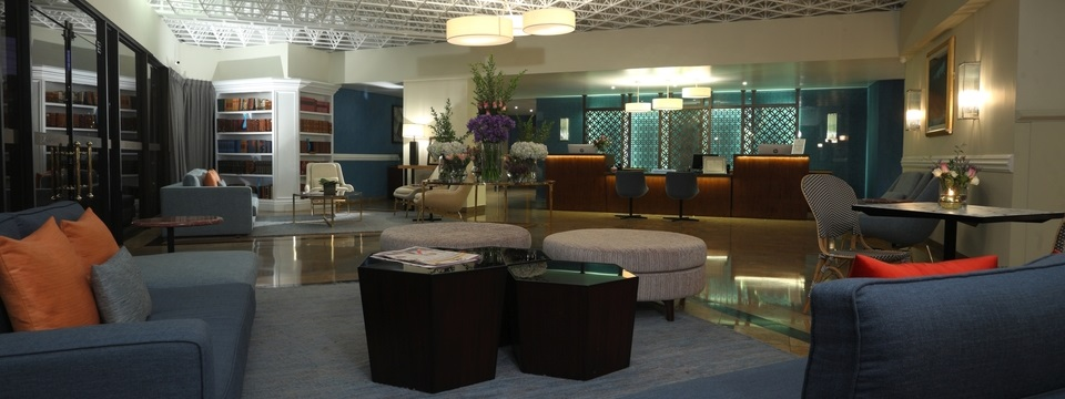 View of entire lobby with seating area, bookshelves and bar