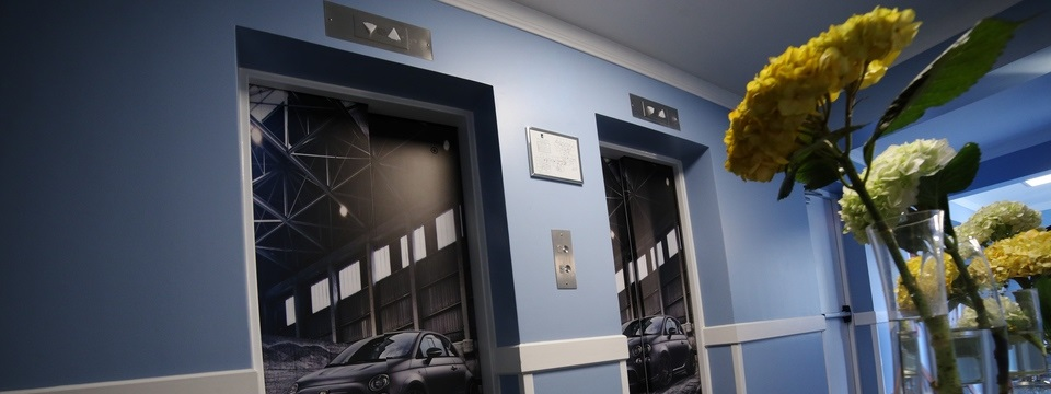 Elevators with pictures of cars in lobby