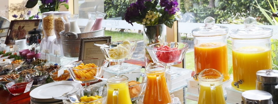 Buffet with fruit and pitchers of juice inside restaurant