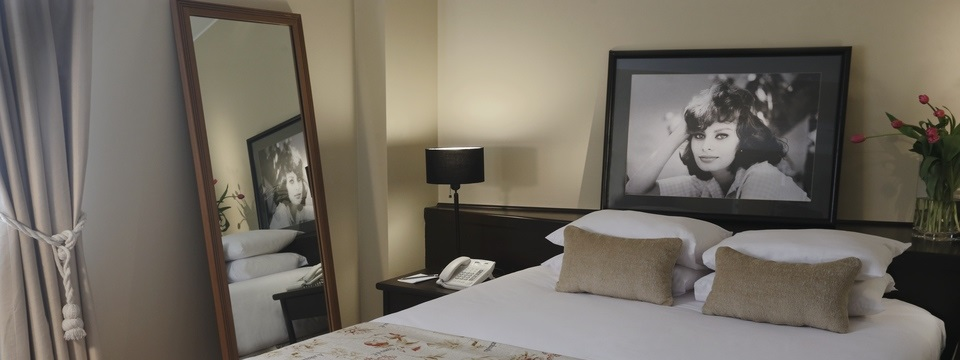 Hotel room with large bed, mirror and black-and-white photograph on wall