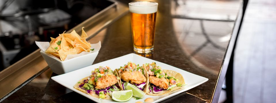 Fish tacos served with tortilla chips and a draft beer