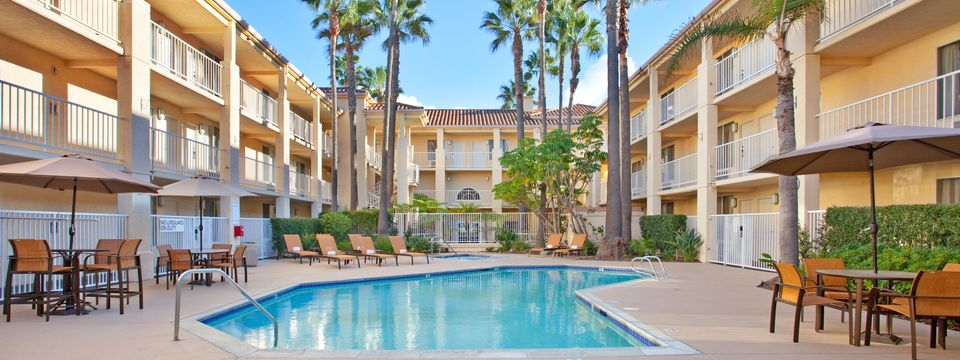 Outdoor pool and hot tub area with palm trees and lounge chairs