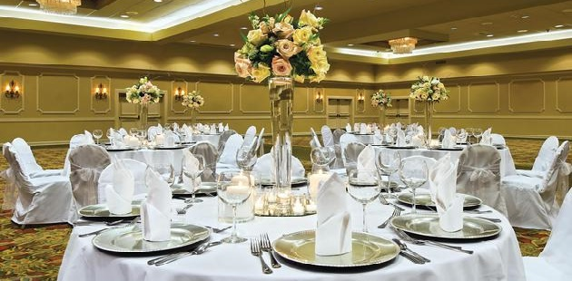 Banquet space featuring round tables with white linens