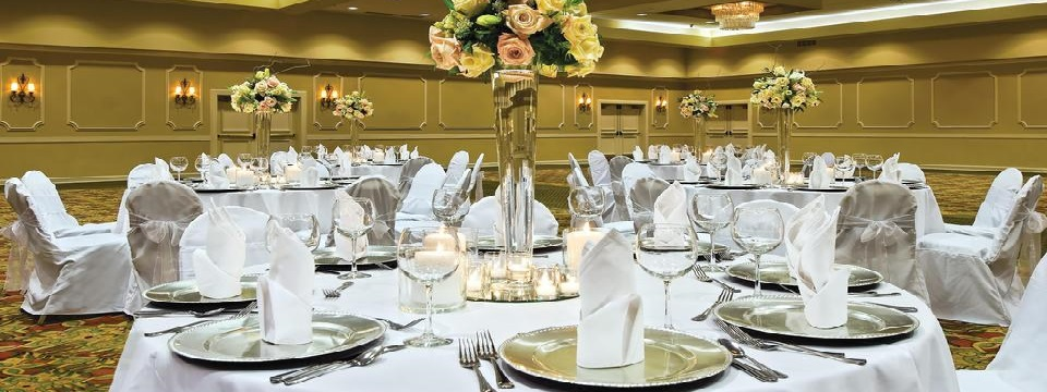 Round tables topped with white linens and floral vase