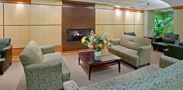 Lobby anchored by sofas, a coffee table and a fireplace