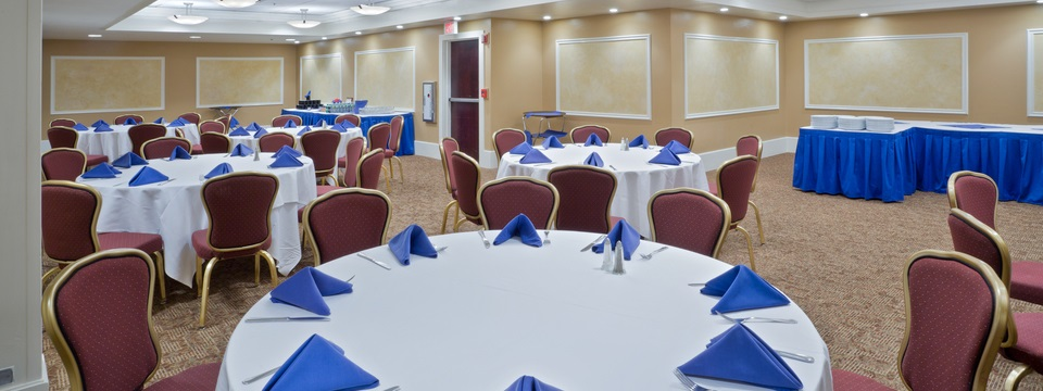Meeting space featuring round tables, white linens and blue napkins