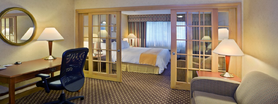 Suite with work desk and French doors separating the bedroom