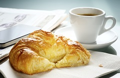 Flaky breakfast croissant with a cup of coffee