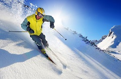 Man in a yellow and blue coat skiing