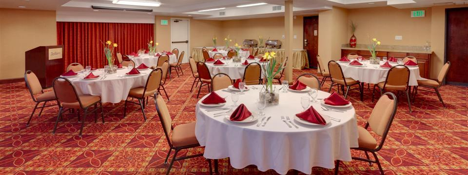 Banquet space with round tables and floral arrangements