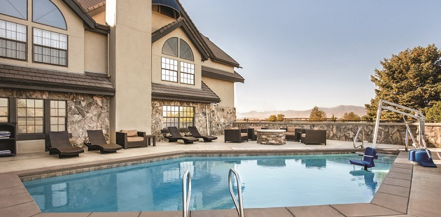Outdoor pool area with brown lounge chairs, a fire pit and a view of the mountains