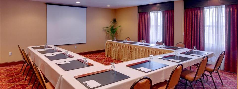 Meeting room with U-shaped table arrangement and presentation screen