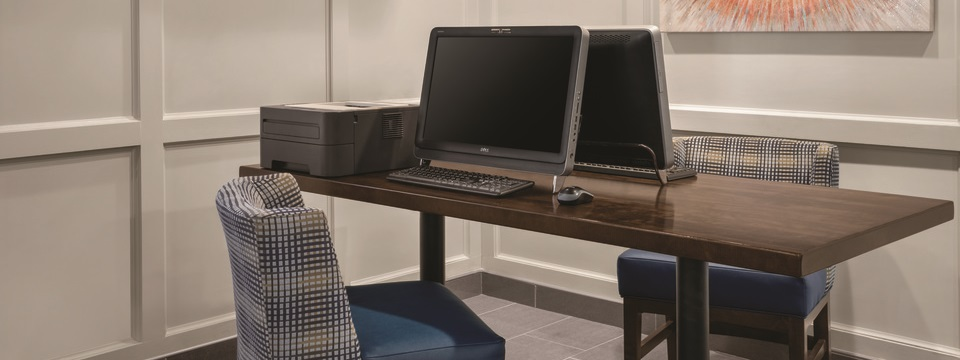Hotel business center with two desktop computers and a printer