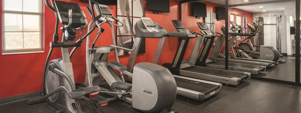 Hotel fitness center with two ellipticals and two treadmills against a red accent wall