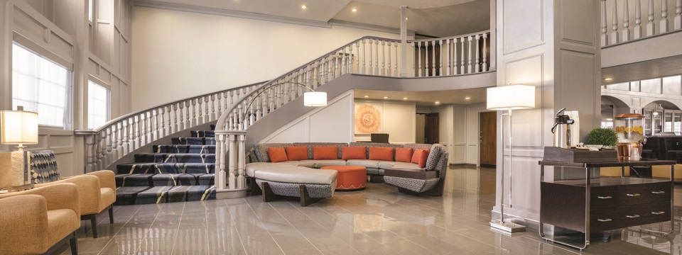 Welcoming lobby featuring comfortable seating and a refreshment table with coffee and citrus water
