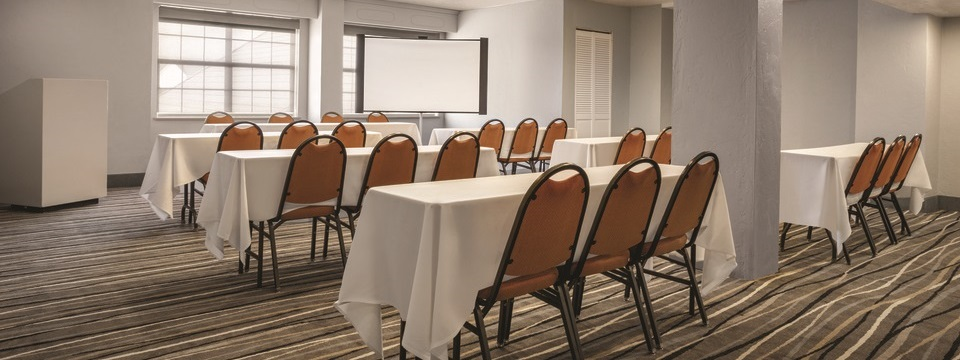 Meeting room with tables and chairs arranged in front of a podium and projection screen