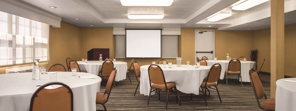 Meeting room with chairs and round tables in front of a podium and projection screen