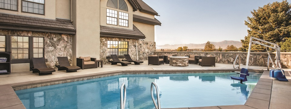 Outdoor pool area featuring brown lounge chairs, a fire pit and a view of the mountains